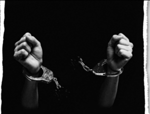 Black and white photo - stark black background. Hands handcuffed, breaking the handcuff chains between them.